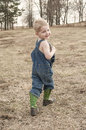 Child in overalls and cowboy boots walking green looking back smiling Stock Photos