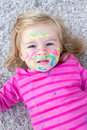 Child with paint on face lying the floor Royalty Free Stock Photos