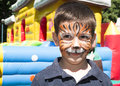 Child with painted face tiger paint boy on children s holiday Royalty Free Stock Image