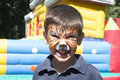 Child with painted face tiger paint boy on children s holiday Royalty Free Stock Photos