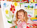 Child painting at easel in art class Stock Images