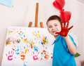 Child painting on easel by hands. Royalty Free Stock Images