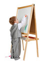 A child paints on an easel in the studio Royalty Free Stock Photography