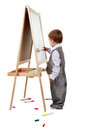 A child paints on an easel in the studio Royalty Free Stock Images