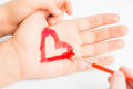 Child paints heart on the hand of mother Royalty Free Stock Photography