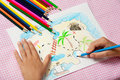 Child paints a picture of pencils pirate treasure map. Royalty Free Stock Photo
