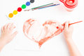 Child paints a red heart on valentine s day Stock Photography