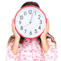 Child in pajamas wearing a clock in place of her face pink holding isolated on white Stock Photos