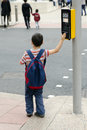 Child at pedestrian crossing a boy standing on a pavement or a side walk pushing the button on the traffic signals for road safety Royalty Free Stock Photo