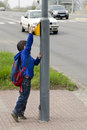 Child at pedestrian crossing school boy pressing a button on car traffic in the background Royalty Free Stock Photography