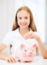 Child with piggy bank education school and money saving concept putting coins into Stock Images