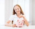 Child with piggy bank education school and money saving concept putting coins into Stock Image