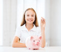 Child with piggy bank education school and money saving concept putting coins into Royalty Free Stock Image
