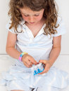 Child placing elastic bands on a band loom small girl wearing braclet Royalty Free Stock Photos