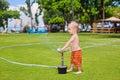 Child play, swim and splash under water sprinkler spray Royalty Free Stock Photo