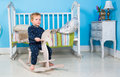 Child play with a wooden rocking toy horse pony Royalty Free Stock Photos