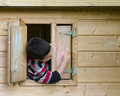 Child in playhouse drawing with chalk on a window shatter of a a Royalty Free Stock Photography