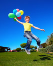 Child playing with balloons in park. Stock Photos
