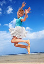 Child playing on beach aganiist blue sky. Stock Image