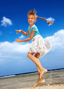 Child playing on beach aganist blue sky. Stock Photos
