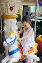 Child playing Carousel horse Royalty Free Stock Photo