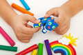 Child playing with colorful clay closeup on hands making animal figures Stock Photo