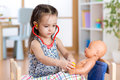 Child playing doctor with doll indoor Royalty Free Stock Photo