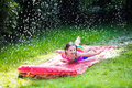Child playing with garden water slide Royalty Free Stock Photo