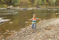 Child playing outside fall season by a river Royalty Free Stock Photo