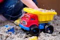 Child Playing with Plastic Truck in Sand Royalty Free Stock Image