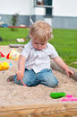 Child playing on playground in sandbox with toys Stock Image