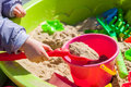 Child playing in sandbox with colorful toys Royalty Free Stock Photo