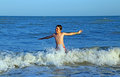 Child playing in sea jumping the waves of choppy sea summer during summer holidays mediterranean Royalty Free Stock Image