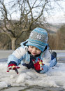Child playing with snow and ice toddler last in early spring Stock Photo