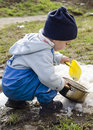 Child playing with snow in spring last and toy spade or shovel a garden early Stock Photos