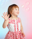 Child playing with soap bubbles Stock Image
