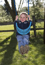 Child playing on swing a toddler a backyard Stock Photos