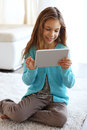 Child playing on tablet pc a carpet at home Stock Photography