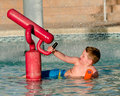 Child playing with water cannon at kiddie pool during summer Stock Image