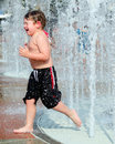 Child playing in water fountains Stock Image