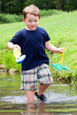 Child plays with boat in creek Stock Images