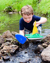 Child plays with boat in creek Royalty Free Stock Photo