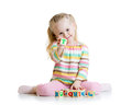 Child plays with building blocks and learning of girl letters Royalty Free Stock Image