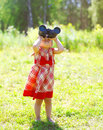 Child plays looks in binoculars outdoors in summer Royalty Free Stock Photo