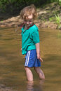 Child plays with water in small river Royalty Free Stock Photography