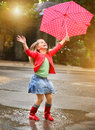 Child with polka dots umbrella wearing red rain boots jumping into a puddle Royalty Free Stock Photography