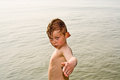Child is posing proudly in the ocean while standing cold sea Stock Photo