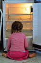 Child poverty hungry poor little girl look for food in empty fridge at home Royalty Free Stock Photography