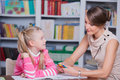 Child psychologist with a little girl draws colored pencils Royalty Free Stock Photo