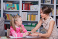 Child psychologist with a little girl draws colored pencils Royalty Free Stock Image